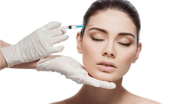 Botox em Curitiba: Paciente do sexo feminino de olhos fechados, enquanto o profissional apoia seu queixo com uma das mãos e lhe aplica a injeção de botox na testa com a outra.