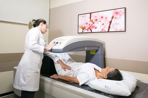 Densitometria Óssea em Curitiba: Médico/Técnico manuseando um aparelho de densitometria em um paciente deitado