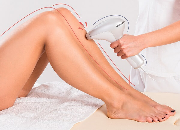 Depilação a Laser em Curitiba: Uma paciente se encontra deitada na maca, com as pernas dobradas e as solas dos pés apoiadas também na maca, enquanto é passado pelo profissional o aparelho que emite os lasers, realizando a depilação nas pernas da mulher.