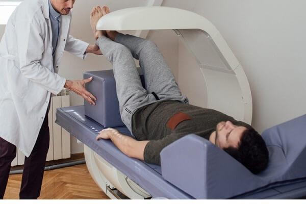 Diagnóstico por Imagem em Curitiba: A imagem mostra um paciente do sexo masculino deitado no aparelho, com as pernas elevadas enquanto um médico posiciona um apoio abaixo de seus pés, facilitando para que este os mantenha elevados durante a realização do exame.
