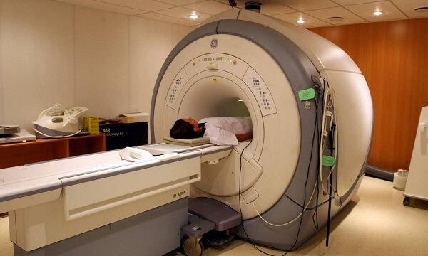 Diagnóstico por Imagem em Curitiba: A imagem mostra uma máquina de ressonância magnética, onde uma paciente se encontra deitada em sua maca, com a metade inferior do corpo dentro do aparelho para a realização das imagens.