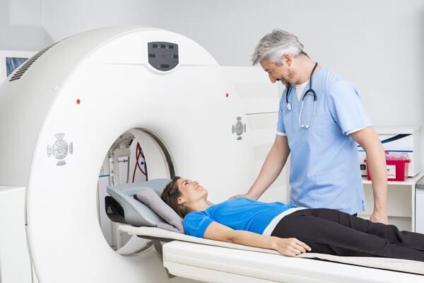 Diagnóstico por Imagem em Curitiba: A imagem mostra uma paciente deitada na maca do equipamento, enquanto ao seu lado se encontra um médico, conversando com a paciente e a preparando para a realização do exame.