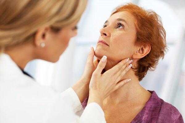 Endocrinologista em Curitiba: A imagem mostra uma paciente com a cabeça erguida, olhando para cima, enquanto uma médica, com ambas as mãos examina sua garganta.