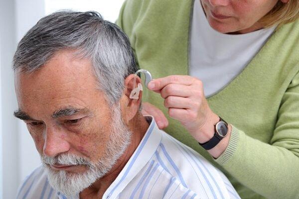 Geriatra em Curitiba: A imagem mostra enquanto um idoso recebe auxílio para colocar o aparelho auditivo. O homem se encontra em frente a pessoa que o está ajudando, olhando para frente enquanto ela posiciona o aparelho em sua orelha.