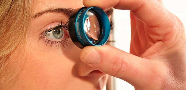 Gonioscopia em Curitiba: Na imagem, um médico oftalmologista aproxima uma lente do olho da paciente, para averiguar o ângulo formado por sua córnea.