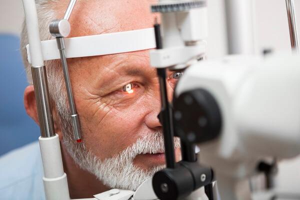 Mapeamento de Retina em Curitiba: A imagem mostra um homem, já idoso, durante a realização do exame. Sua cabeça se encontra apoiada no suporte, enquanto a máquina em sua frente emite uma luz em seu olho, realizando o mapeamento.
