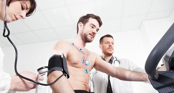 Medicina Esportiva em Curitiba: A imagem retrata um paciente durante seu teste de esforço, enquanto uma médica do esporte acompanha sua pressão, e outro seus batimentos, cada um posicionado de um lado do atleta.