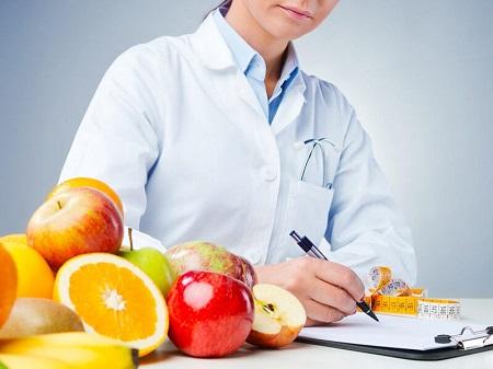 Nutricionista em Curitiba: A imagem mostra uma médica nutricionista escrevendo em uma prancheta, enquanto em primeiro plano temos diversas frutas, remetendo a uma alimentação saudável.