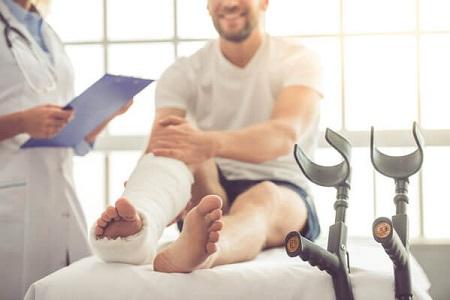 Traumatologista em Curitiba: A imagem mostra um paciente na maca, conversando com um profissional Traumatologista. o Pé direito do paciente se encontra engessado, enquanto em primeiro plano aparecem suas muletas em destaque.