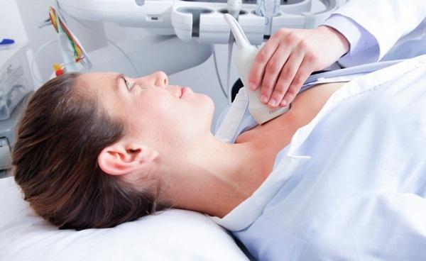 Ultrassom em Curitiba: Na imagem, a paciente encontra-se deitada na maca, olhando em direção à profissional que está realizando o exame com o ultrassom em sua região torácica.